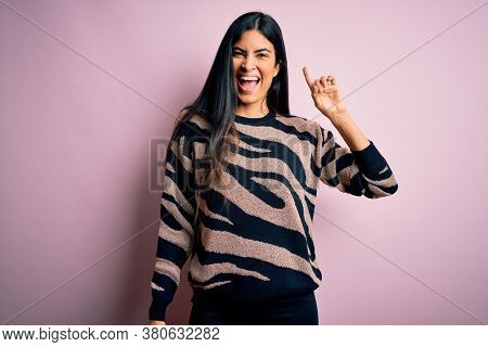 Young beautiful hispanic woman wearing animal print sweater over pink background pointing finger up with successful idea. Exited and happy. Number one.