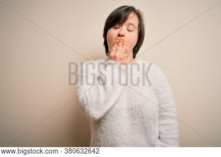 Young down syndrome woman standing over isolated background bored yawning tired covering mouth with hand. Restless and sleepiness.