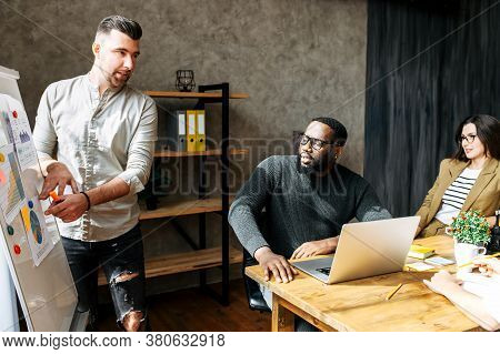 Presentation In A Multiracial Team In Contemporary Office. A Condfident Attractive Guy In Casual Wea