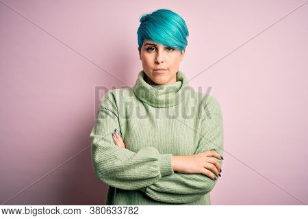 Young beautiful woman with blue fashion hair wearing casual turtleneck sweater skeptic and nervous, disapproving expression on face with crossed arms. Negative person.