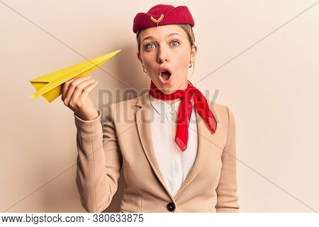 Young beautiful blonde woman wearing stewardess uniform holding paper plane scared and amazed with open mouth for surprise, disbelief face