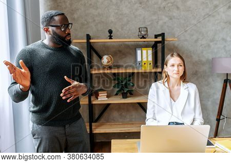 Midshot Of Two Multiracial Colleagues In Office. An Afro-american Young Man Gives His Employees Task