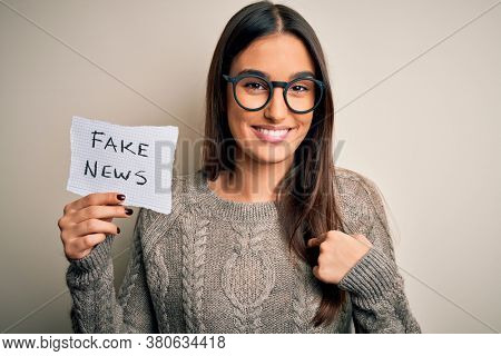 Young beautiful brunette woman wearing glasses holding paper with fake news message with surprise face pointing finger to himself