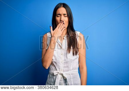 Young beautiful brunette woman wearing casual dress over isolated blue background bored yawning tired covering mouth with hand. Restless and sleepiness.