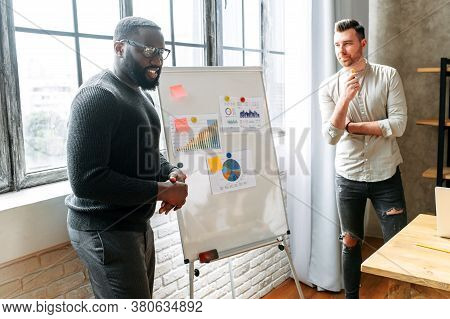 Two Multiracial Colleagues Conducting A Presentation On The Flipchart Beside The Window. A Young Guy