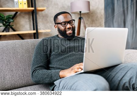 Cheerful African-american Guy Sits On Sofa In Modern Living Room Alone And Using Trendy Laptop For N