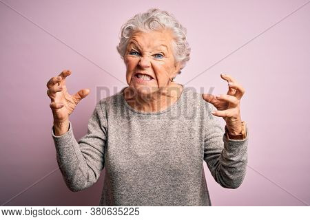 Senior beautiful woman wearing casual t-shirt standing over isolated pink background Shouting frustrated with rage, hands trying to strangle, yelling mad