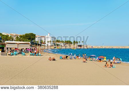 HOSPITALET DEL INFANT, SPAIN - JULY 24, 2020: People at the Arenal Beach in Hospitalet del Infant, during the pandemic Covid-19 situation, where groups of people should keep a distance of 2 meters