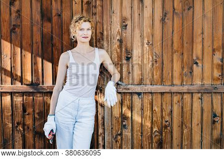 Mature Woman Portrait, With Curly Blonde Hair Leaning Against A Wooden Garage Door.