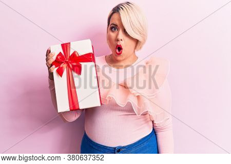 Young beautiful blonde plus size woman holding birthday gift over isolated pink background scared and amazed with open mouth for surprise, disbelief face