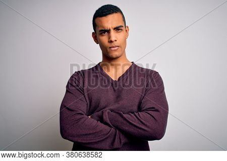Young handsome african american man wearing casual sweater over white background skeptic and nervous, disapproving expression on face with crossed arms. Negative person.