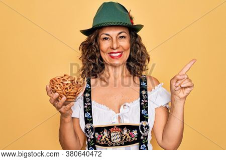 Middle age woman wearing traditional octoberfest dress holding bowl with baked pretzels very happy pointing with hand and finger to the side