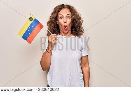 Middle age beautiful tourist woman holding venezuelan flag over isolated white background scared and amazed with open mouth for surprise, disbelief face