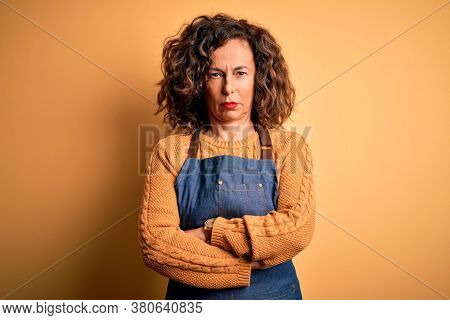 Middle age beautiful baker woman wearing apron standing over isolated yellow background skeptic and nervous, disapproving expression on face with crossed arms. Negative person.