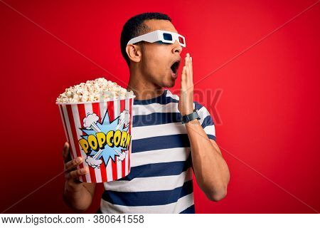 Young handsome african american man watching movie using 3d glasses eating popcorns bored yawning tired covering mouth with hand. Restless and sleepiness.