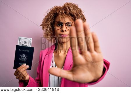 Young african american curly woman holding united states passport with dollars banknotes with open hand doing stop sign with serious and confident expression, defense gesture