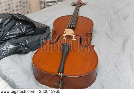 A  Cello Abandoned On The Bed Next To Plastic Bag