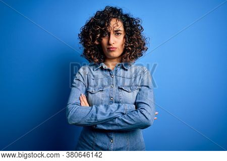 Young beautiful curly arab woman wearing casual denim shirt standing over blue background skeptic and nervous, disapproving expression on face with crossed arms. Negative person.