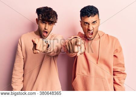 Young gay couple wearing casual clothes pointing displeased and frustrated to the camera, angry and furious with you