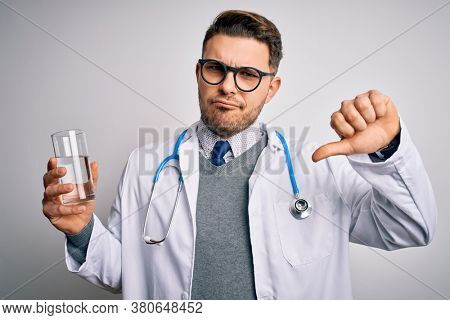 Young doctor man wearing medical coat holding a glass of fresh water over isolated background with angry face, negative sign showing dislike with thumbs down, rejection concept