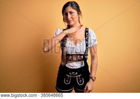 Young beautiful brunette german woman celebrating Octoberfest wearing traditional dress cutting throat with hand as knife, threaten aggression with furious violence