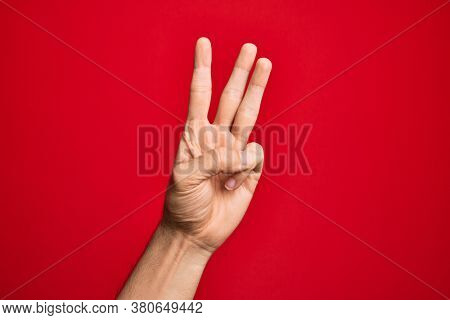 Hand of caucasian young man showing fingers over isolated red background counting number 3 showing three fingers