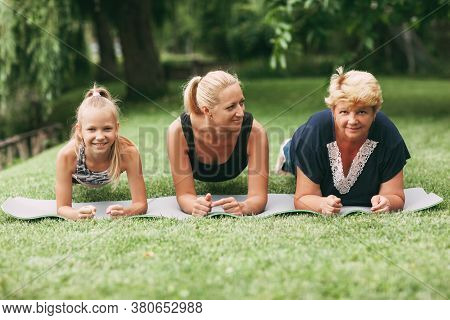 Grandmother, Mom And Child Are Doing Fitness Together In Nature. Go In For Sports. Healthy Lifestyle