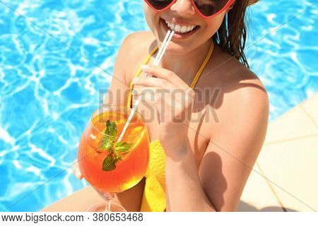 Woman With Glass Of Refreshing Drink Near Swimming Pool, Closeup