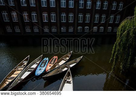 Canoes Moored Outside Riverside Apartments. Lightly Simplified River Lifestyle Image Of Canoe Boats