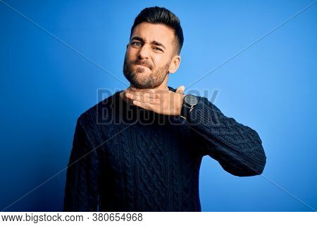 Young handsome man wearing casual sweater standing over isolated blue background cutting throat with hand as knife, threaten aggression with furious violence