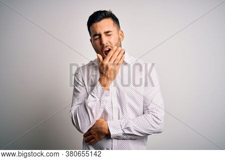 Young handsome man wearing elegant shirt standing over isolated white background bored yawning tired covering mouth with hand. Restless and sleepiness.