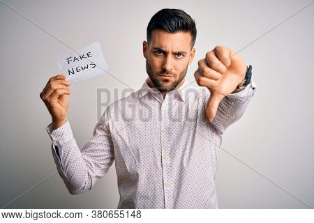 Young business man holding fake news paper over isolated background with angry face, negative sign showing dislike with thumbs down, rejection concept