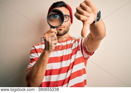 Young detective man looking through magnifying glass over isolated background with angry face, negative sign showing dislike with thumbs down, rejection concept