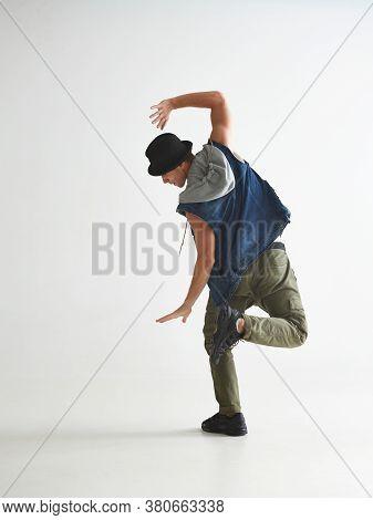 Cool Guy Breakdancer In Hat Dancing Hip-hop In Studio Isolated On White Background. Break Dance Less