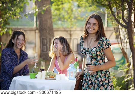 Pretty Happy Young Woman Staying Naer The Table With Glass Of Red Wine In Her Hand. Two Smilling Fem