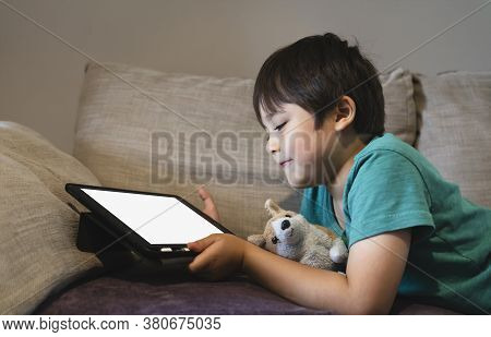 Cropped Shot Kid Lying On Sofa Watching Cartoons On Tablet,6-7 Year Old Boy Playing Game On Touch Pa