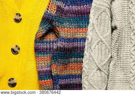 Bunch Or Pile Of Stylish Cozy Knitted Color Sweaters With Different Knitting Patterns.texture Of Woo