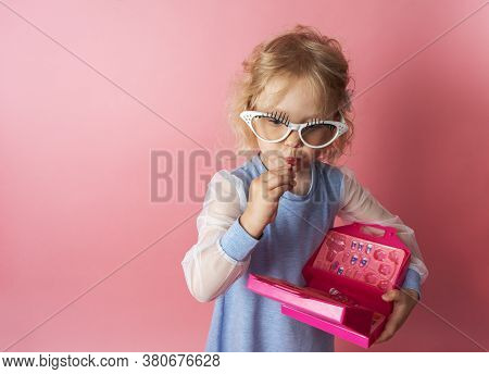 Little Girl Child Plays With A Set Of Baby Cosmetics And Uses Lipstick.
