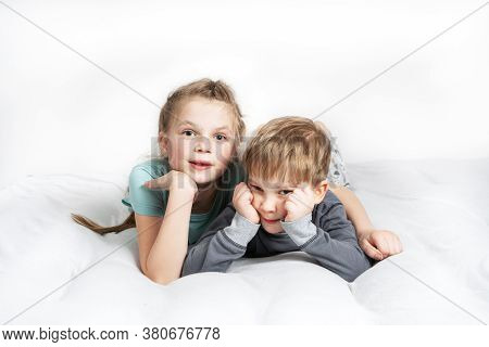 Friendship: A Boy And A Girl Are Lying On The Bed Propping Their Chin In Their Hand.