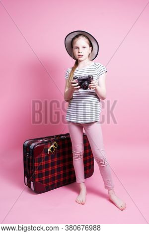 Travel: A Little Girl In A Straw Hat With A Big Kars Suitcase Is Waiting For A Trip.