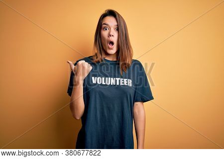 Young beautiful brunette girl doing volunteering wearing t-shirt with volunteer message word Surprised pointing with hand finger to the side, open mouth amazed expression.