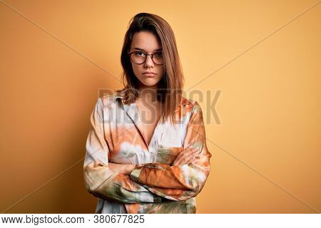 Young beautiful brunette girl wearing casual shirt and glasses over isolated yellow background skeptic and nervous, disapproving expression on face with crossed arms. Negative person.