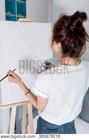 Woman Artist In A White T-shirt, View From The Back, At Home In A Workshop, In Her Hand A Brush And