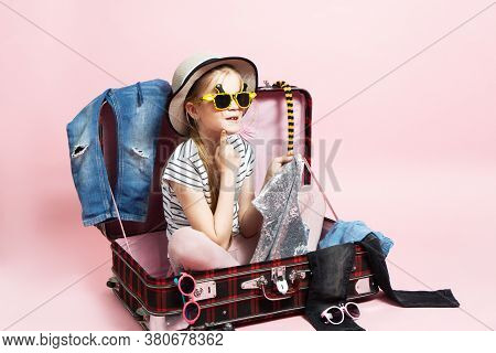 Travel: A Schoolgirl Girl Prepares For A Trip And Collects Clothes In A Large Suitcase.