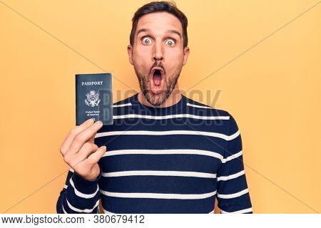 Young handsome tourist man holding united states passport over isolated yellow background scared and amazed with open mouth for surprise, disbelief face