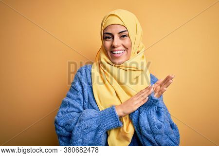 Young beautiful brunette muslim woman wearing arab hijab over isolated yellow background clapping and applauding happy and joyful, smiling proud hands together