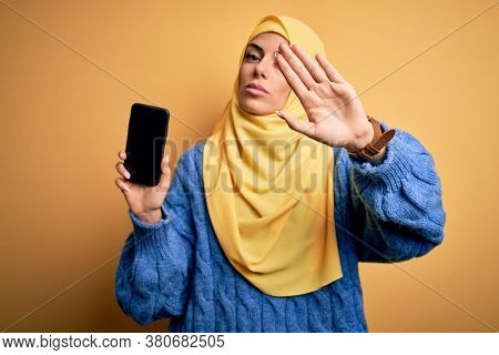 Young beautiful brunette arab woman wearing islamic hijab holding smartphone showing screen with open hand doing stop sign with serious and confident expression, defense gesture