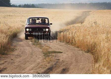 SHARKAN, RUSSIA - JULY 29, 2010: Retro car moves on the rural dusty road in wheat field