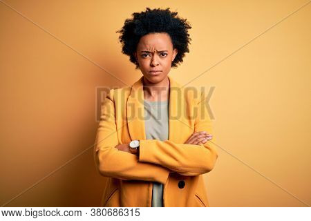 Young beautiful African American afro businesswoman with curly hair wearing yellow jacket skeptic and nervous, disapproving expression on face with crossed arms. Negative person.