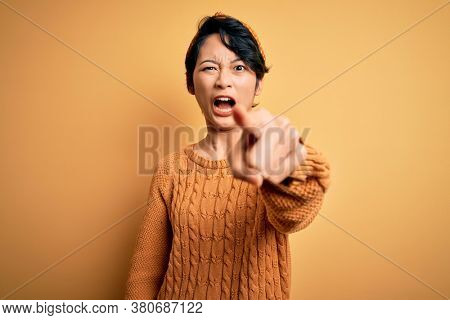 Young beautiful asian girl wearing casual sweater and diadem standing over yellow background pointing displeased and frustrated to the camera, angry and furious with you